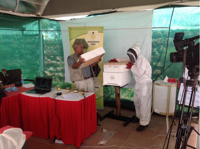 ABL CEO Ernest Simeone with one of his workers demonstrating to HiH EA members how to mount a modern beehive.